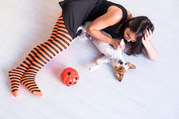 カボチャと彼女の所有者と一緒に床に横たわっている犬の平面図。黒とオレンジのタイツを着ている女性。ハロウィーンのコンセプト。屋内でのライフスタイル