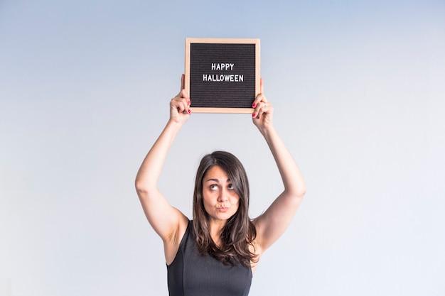 幸せなハロウィーンのサインと黒のビンテージレターボードを保持している若い女性。屋内でのライフスタイル