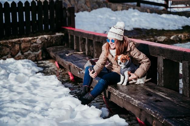 女性と雪で山で屋外を楽しんでいるかわいいジャックラッセル犬。冬のシーズン。携帯電話でセルフポートレートを取る女性