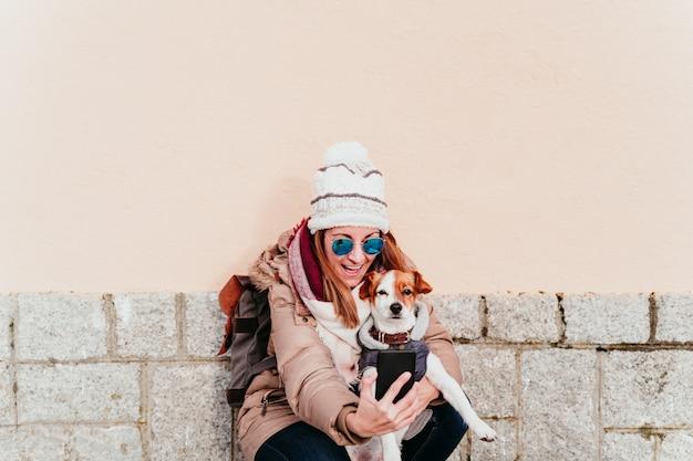 彼女のかわいい犬を屋外でセルフポートレートを取る女性。技術とペットのコンセプト