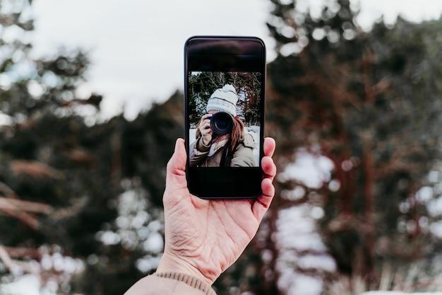 Женщина на горе, принимая автопортрет на мобильном телефоне с камерой. зимний сезон