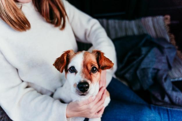 車に山で屋外を楽しむ女性とかわいいジャックラッセル犬。旅行のコンセプト。冬の季節