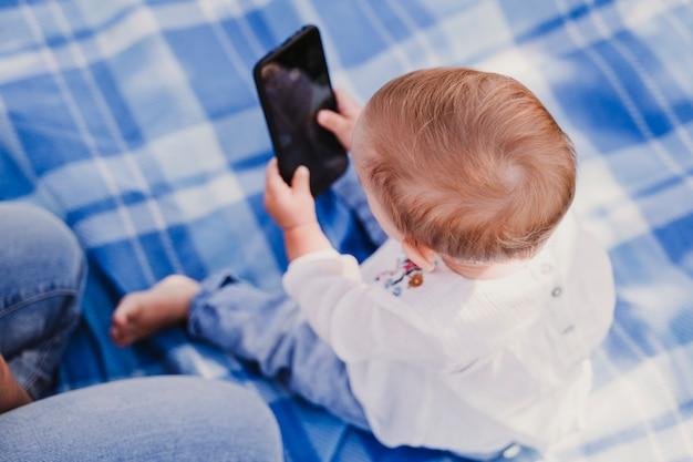 Молодая мать и счастливый ребенок, с помощью мобильного телефона на открытом воздухе. концепция технологии
