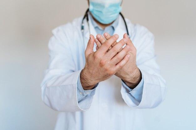 Доктор, носящий защитную маску и применяющий спиртовой гель