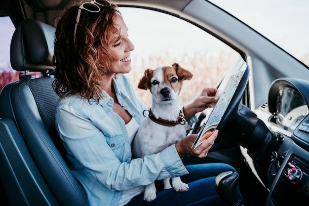 車の中で地図を読む若い美しい女性。旅行のコンセプト。かわいいジャックラッセル犬のほか。