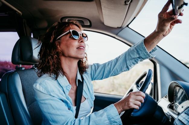 車を運転して、リアミラーを調整する若い美しい女性。旅行の概念