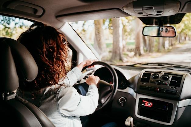 車を運転する若い美しい女性。旅行のコンセプト。内部からの眺め。木の道