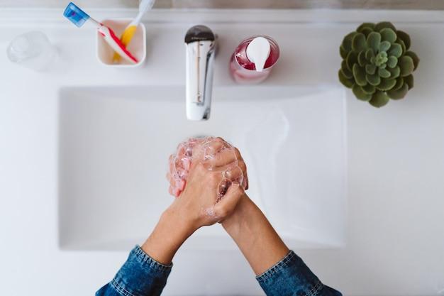 До неузнаваемости женщина моет руки на раковину с мылом.