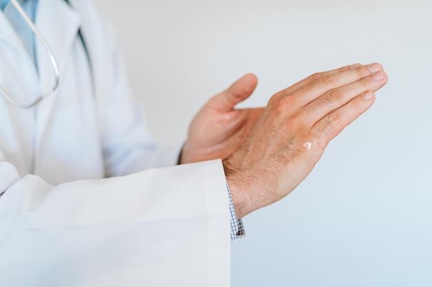 Кавказский доктор носить защитную маску и перчатки в помещении. использование спиртового геля или антибактериального дезинфицирующего средства. концепция гигиены и вируса короны