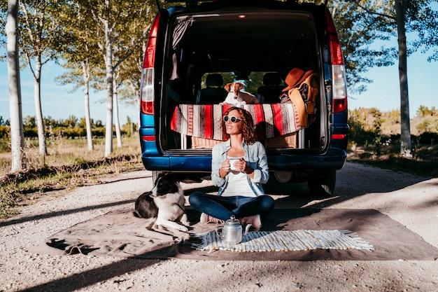 Молодая красивая женщина, пить кофе или чай, кемпинг на открытом воздухе с фургоном и ее двумя собаками. концепция путешествия