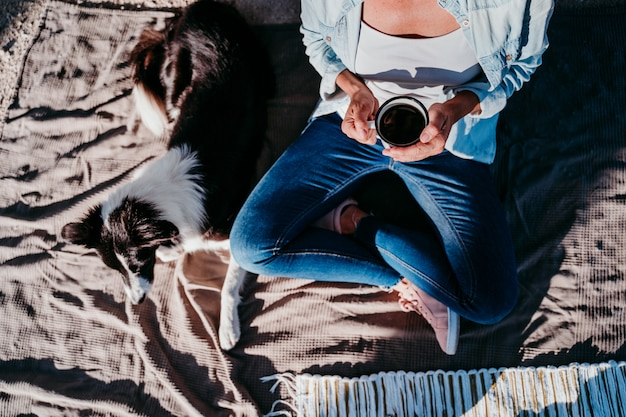 Молодая красивая женщина, пить кофе или чай, кемпинг на открытом воздухе с фургоном и ее двумя собаками. концепция путешествия. вид сверху