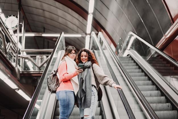 Двое друзей ждут, когда спускаются по лестнице на вокзал, прежде чем сесть на поезд. используя мобильный телефон. туристическая фотография