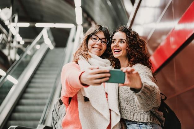 Двое друзей ждут, когда спускаются по лестнице на вокзал, прежде чем сесть на поезд. принимая селфи с мобильного телефона. туристическая фотография
