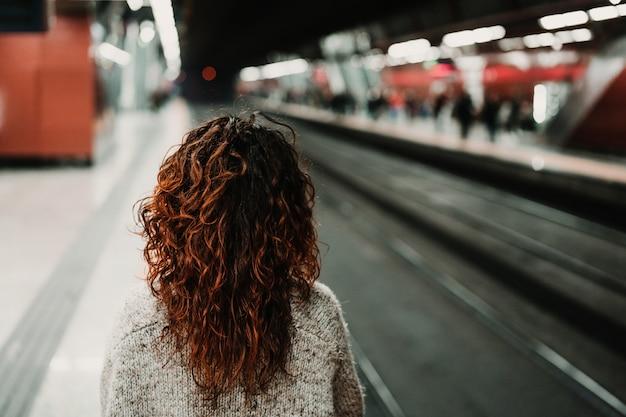 Молодая красивая женщина на вокзале с помощью мобильного телефона, прежде чем сесть на поезд. вид сзади. путешествия, технологии