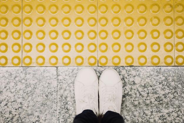 Вид сверху ног женщины на вокзале, готовом сесть на поезд, желтый пол с рельефом для обозначения конца платформы