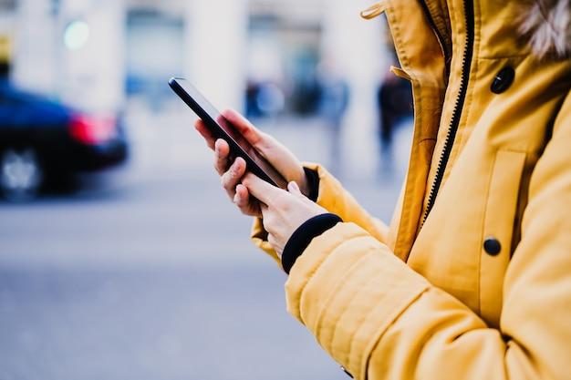 До неузнаваемости турист женщина с помощью мобильного телефона на открытом воздухе на улице. концепция образа жизни и путешествий
