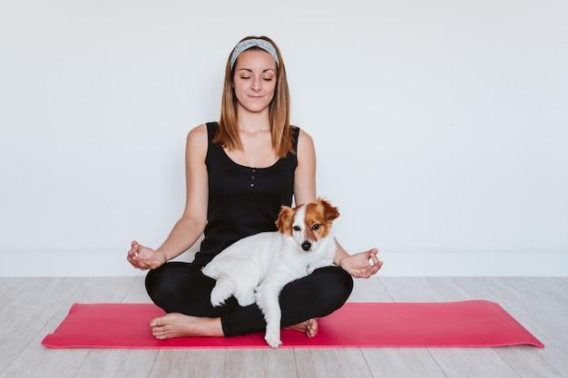 Симпатичная маленькая собачка джек рассел лежит на коврике для йоги у себя дома со своей хозяйкой