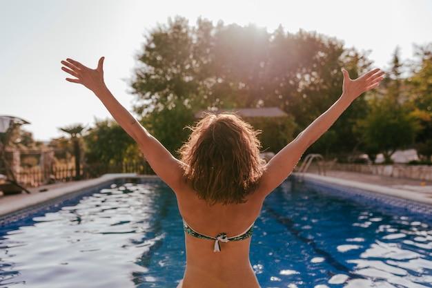 Молодая красивая женщина, расслабиться в бассейне на закате. вид сзади