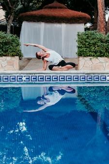 プールサイドでヨガをやっている若い女性