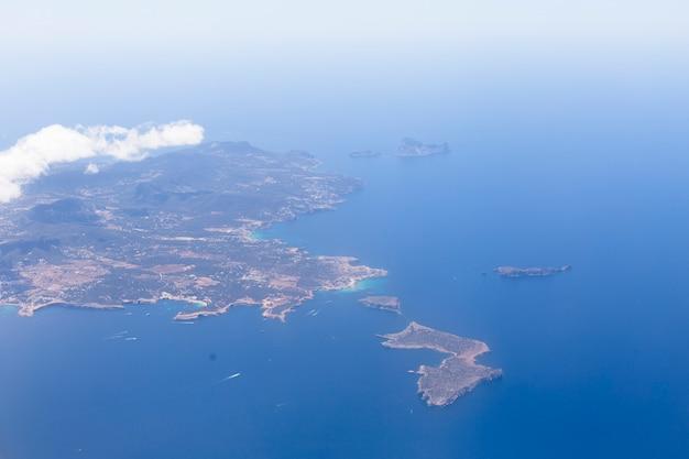 青い美しい水とイビサ島の飛行機からの眺め。雲。休日と夏のコンセプト