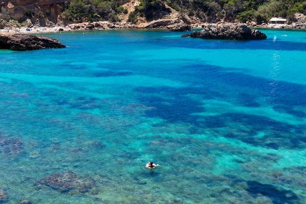 平らなドーナツに浮かぶ女性と晴れた日の青い海のイビサの美しい風景。夏と休日のコンセプトです。