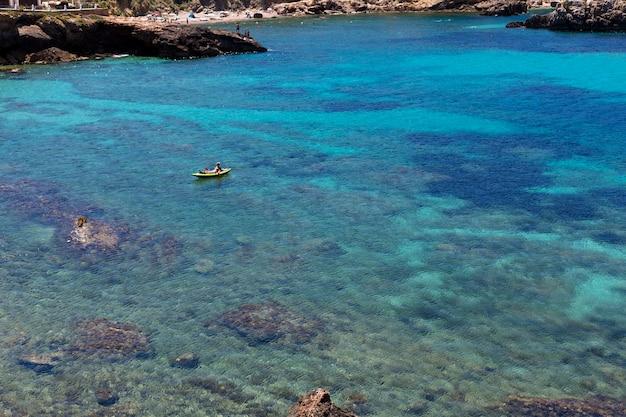 パドルサーフィンを練習している男と晴れた日に青い海のイビサの美しい風景。夏と休日のコンセプトです。