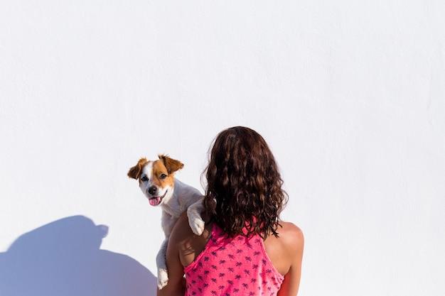 白い壁にかわいい小型犬を抱えている女性の背中。夏の日の日没。