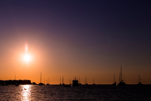 Красивый силуэт лодок в порту на закате в ибице. праздники и летняя концепция