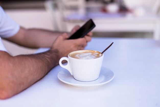 テラスのテーブルでコーヒーのカップを持つスマートフォンを保持している男性の手。昼間、ライフスタイル