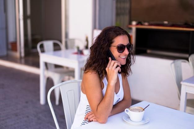 テラスで朝食をとり、彼女の携帯電話で話し、笑顔の女性。朝、昼、テクノロジー