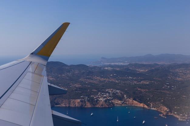 飛行中の窓面からの空撮。スペインの上のイビサの風景。旅行のコンセプト