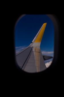 飛行中の窓面からの空撮。青い空と雲の背景。旅行のコンセプト