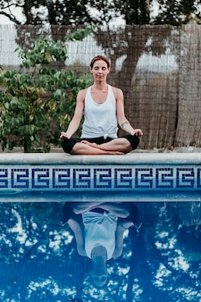 スイミングプールで若い女性(フィットネス、ヨガ、健康な体)の肖像