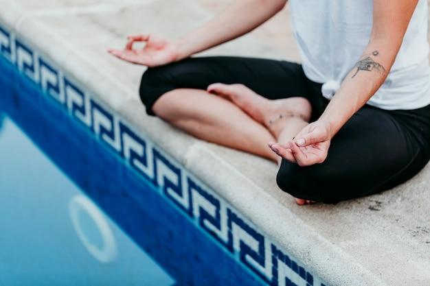 スイミングプールで認識できない若い女性(フィットネス、ヨガ、健康な体)