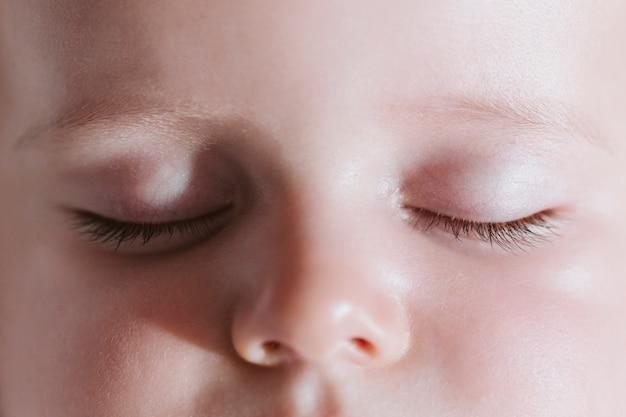 眠っている赤ちゃんのビューを閉じます。目を閉じて休んでいます。赤ちゃんと家族の概念。