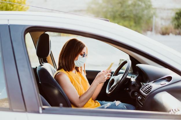 防護マスクを身に着けている携帯電話を使用して車の中で若い女性