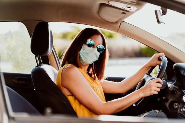 防護マスクを身に着けている車の中で若い女性