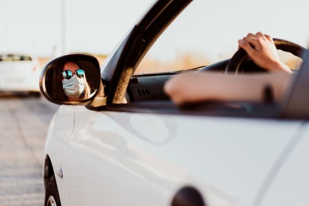 防護マスクを身に着けている車の中でリラックスした若い女性