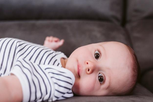 ソファに横になっていると、カメラを見て美しい男の子の肖像画を閉じる