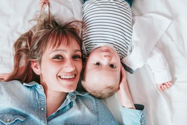 幸せな若い母親と彼女の男の子がベッドに横になっていると笑顔