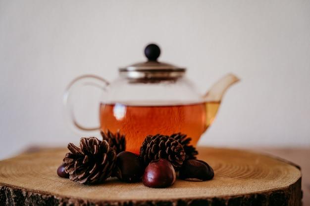 木製のテーブルにお茶とティーポット。さらにパイナップルと栗。朝、昼。秋の季節