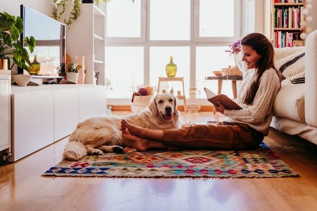 自宅で健康的な朝食中にコーヒーを楽しんでいる美しい女性。ノートに書く。他にも愛らしいゴールデンレトリバー犬。屋内でのライフスタイル