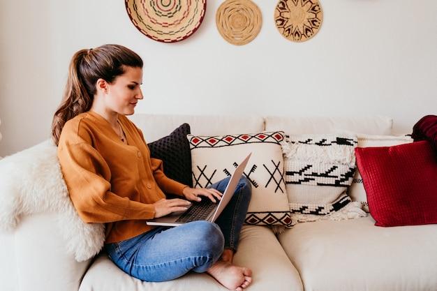 Молодая женщина работает на ноутбуке дома. милый золотистый ретривер