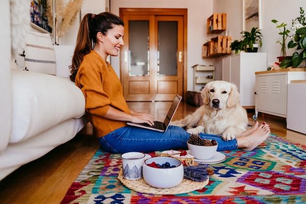 若い女性が自宅のラップトップに取り組んでいます。かわいいゴールデンレトリバーの犬。