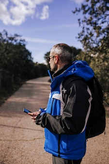 自然の中で屋外で携帯電話を使用して白人の男。晴れた日
