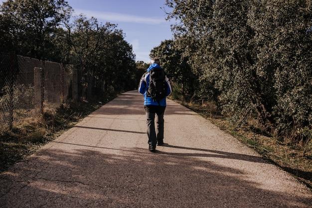 自然の中で道を歩いている白人の男。晴れた日。背面図