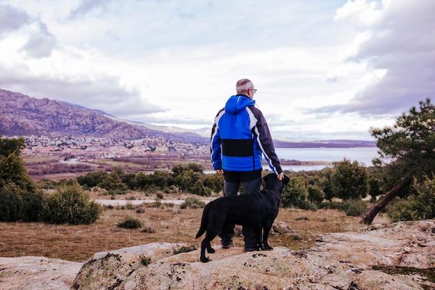 岩の上に彼の黒いラブラドールと山で若いハイカー男。曇りの冬の日。背面図
