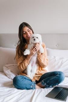 自宅で彼女のかわいい犬と遊ぶ美しい女性
