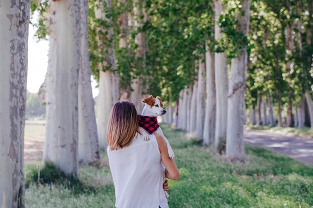 Молодая красивая женщина, держа ее милая маленькая собака на плече. на открытом воздухе. любовь к животным концепции и образ жизни на открытом воздухе