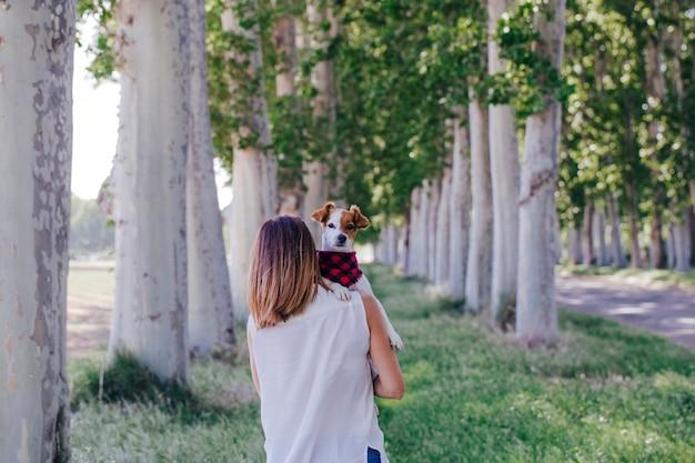 肩に彼女のかわいい小型犬を保持している若い美しい女性。屋外。動物のコンセプトとライフスタイルアウトドアが大好き
